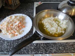 Desmenuzado el pescado y picadas las gambas se fríe la cebolla