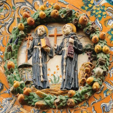 """Inmediatamente encima de éste se muestra el de San Buenaventura y San Antonio de Padua. Ambos con hábito oscuro, atados con cíngulos blancos de gruesos nudos, aparecen nimbados en color amarillo. El primero de éstos en su mano derecha porta una cruz patada y en su mano izquierda un libro, en alusión a su tratado """"Lignum vitae"""", el primero de estos símbolos es antecedente de su """"crucifijo biblioteca"""", que más tarde se convertiría en su distintivo más personal, la mitra episcopal de diversos colores y el capelo cardenalicio en verde terminan de conformar su iconografía."""